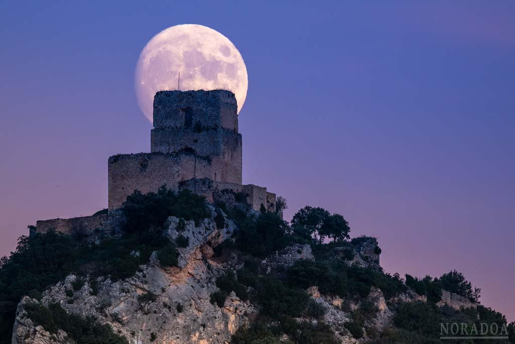 La luna saliendo detrás del castillo de Lanos en el pueblo alavés de Ocio