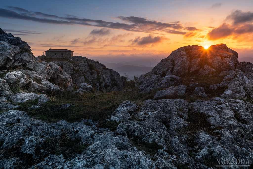 Cima del monte Aitzorrotz con la ermita de Santa Cruz al amanecer