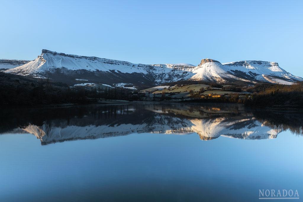 La sierra Salvada/Gorobel nevada se refleja en embalse de Maroño